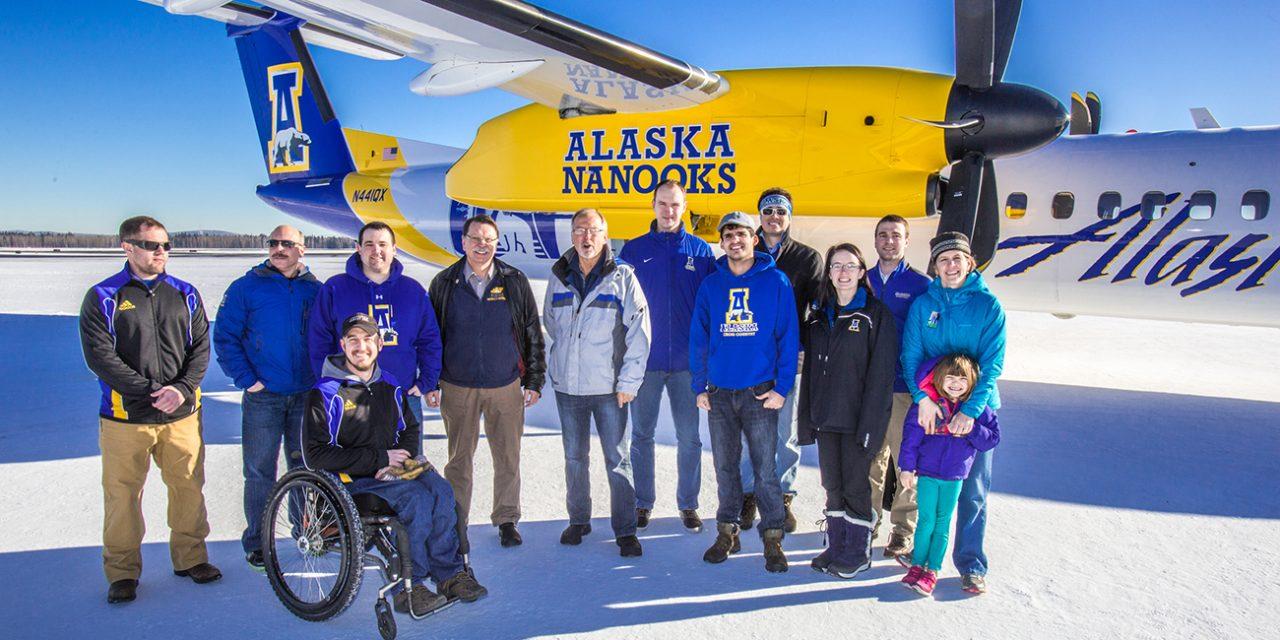 Coaches, athletic department staff and UAF administrators pose Alaska Airlines Bombardier Dash 8-Q400 UAF Livery
