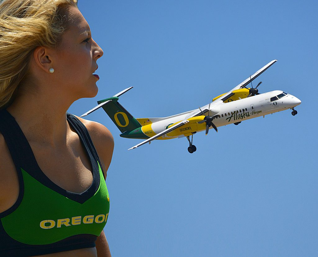 Oregon Ducks cheerleader watches an Alaska Airlines (Horizon) plane Q400 painted with the Ducks Logo and colors