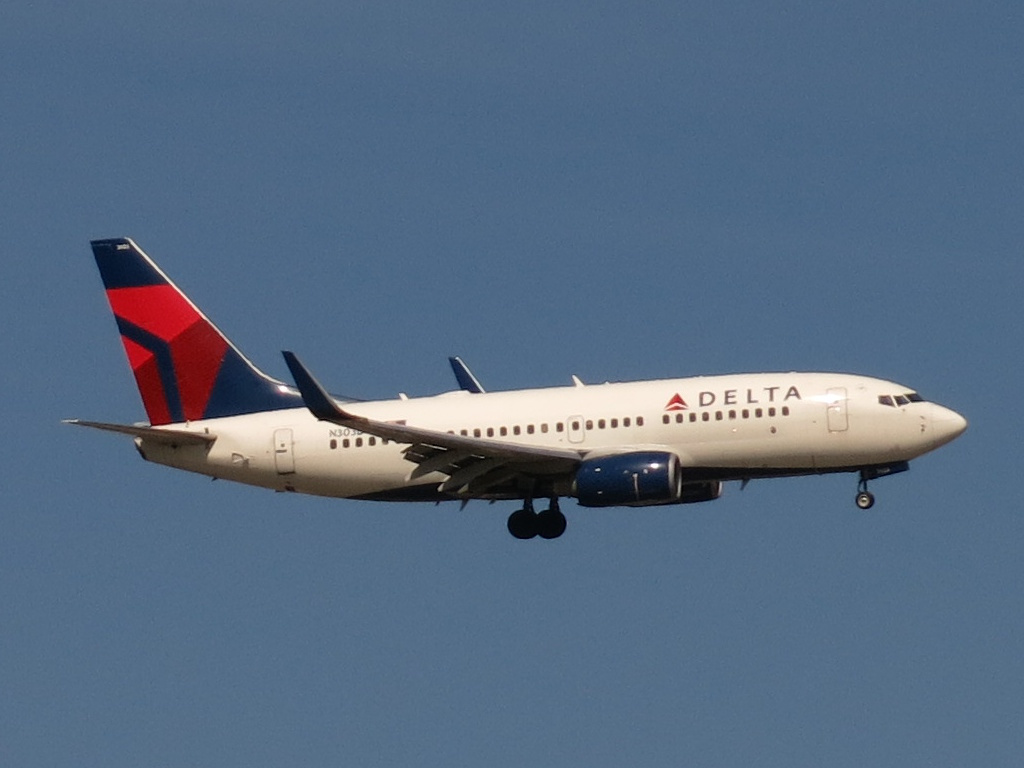 Delta Air Lines Boeing 737-732 N303DQ is on final approach to John F. Kennedy International Airport's Runway 13L, arriving from Bogota, Colombia.