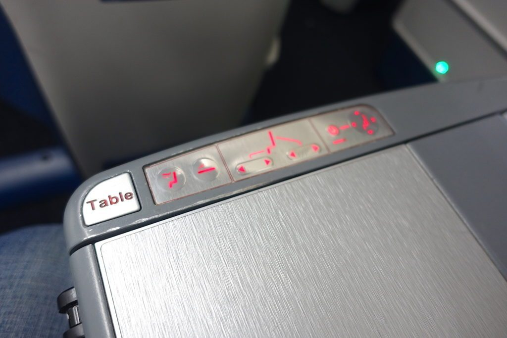 Delta Air Lines Boeing 767-400ER Business Class (DELTA ONE) cabin armrest has the seat controls, a table and a remote control for the entertainment system