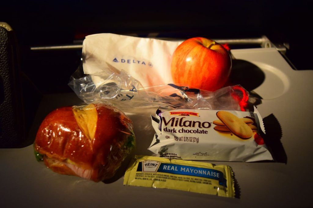 Delta Air Lines Fleet Boeing 777-200ER Premium Economy (Comfort+) snack bag, which contained a ham and cheese sandwich, apple, Milano cookies, and mayonnaise