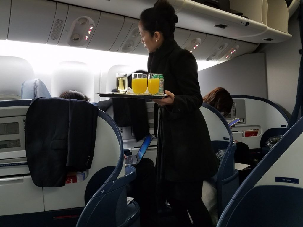 Delta Air Lines Fleet Boeing 777-200LR business elite:Delta ONE class cabin pre-departure drinks services