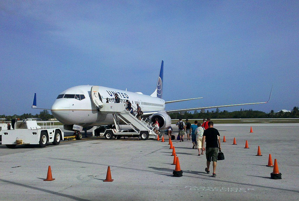 Passengers boarding United Airlines Boeing 737-824(WL) aircraft (N33284; United fleet number 0284) via airstairs on the tarmac at Owen Roberts International Airport