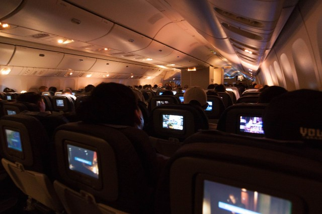 United Airlines Fleet Widebody Aircraft Boeing 777 200 Economy Class cabin long haul flight lights are dimmed for take off