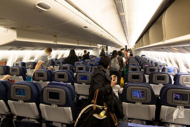 United Airlines Fleet Widebody Aircraft Boeing 777 200 Economy Class cabin long haul flight passenger disembark after landing photos