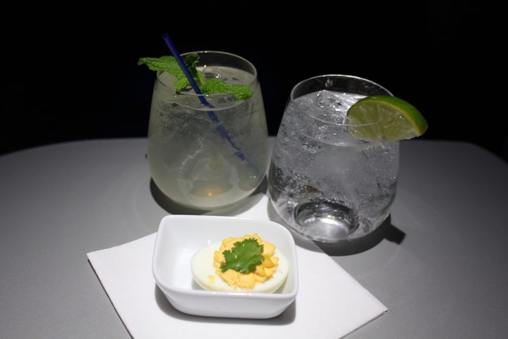 Airbus A321 200 JetBlue Airways Mint Suite Experience Business Class Cabin cocktail with deviled egg appetizer and sparkling water
