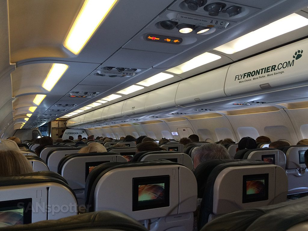 Frontier Airlines Airbus A319 100 Economy cabin standard seating inflight view with frontier logo on headbin