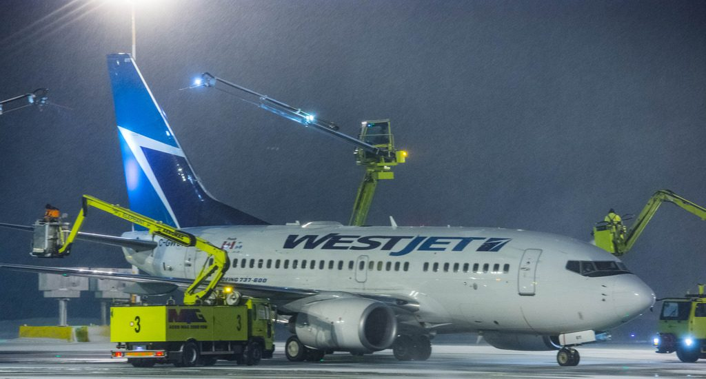 Boeing 737 6CT C GWCY WestJet Airlines deicing at Ottawa International Airport