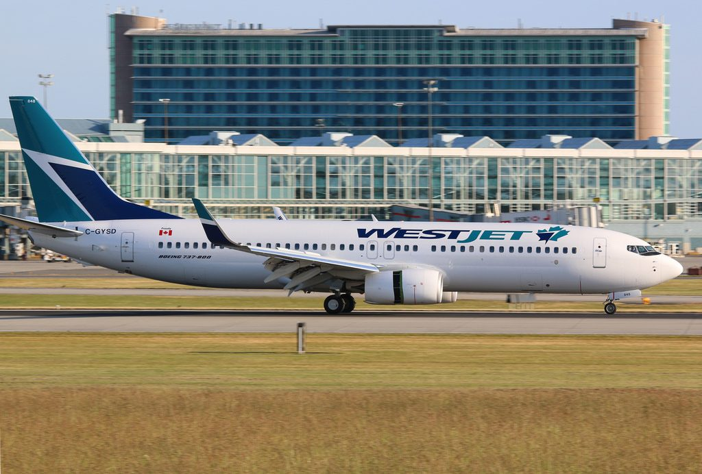 WestJet Boeing 737 8CT C GYSD color scheme with YVR Fairmont YVR Hotel